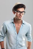 Young man wearing glasses. Handsome man in blue shirt, wearing glasses, on gray background Stock Photo