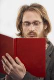 Young man wearing glasses reading a book. Young blond handsome man with glasses is reading a book. Shot in studio Royalty Free Stock Image