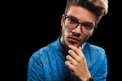 Young man wearing glasses while thinking and posing Royalty Free Stock Images
