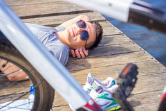 Young man wearing in gray shirt with glasses  listening music headphones  lying at the beach and resting after bicycle ride.  Royalty Free Stock Photos