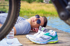 Young man wearing in gray shirt with glasses  listening music headphones  lying at the beach and resting after bicycle ride.  Stock Photo