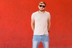 Young man wearing gray t-shirt near color wall. On street Stock Image