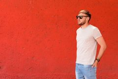 Young man wearing gray t-shirt near color wall. On street Stock Photography