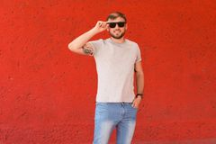 Young man wearing gray t-shirt near color wall. On street Royalty Free Stock Image