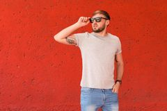 Young man wearing gray t-shirt near color wall. On street Royalty Free Stock Photo