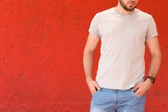 Young man wearing gray t-shirt near color wall. On street Royalty Free Stock Photos
