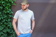 Young man wearing gray t-shirt near wall. On street. Urban style Royalty Free Stock Photos