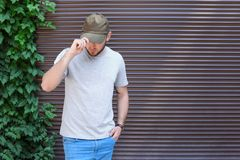 Young man wearing gray t-shirt near wall on street. Urban style Stock Photography