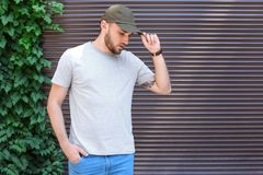 Young man wearing gray t-shirt near wall on street. Urban style Royalty Free Stock Photos