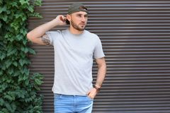 Young man wearing gray t-shirt near wall. On street. Urban style Stock Images