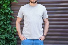 Young man wearing gray t-shirt near wall. On street. Urban style Stock Image