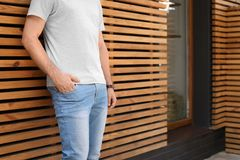 Young man wearing gray t-shirt near wooden wall on street. Urban style Stock Photo