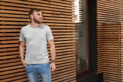 Young man wearing gray t-shirt near wooden wall. On street. Urban style Royalty Free Stock Images