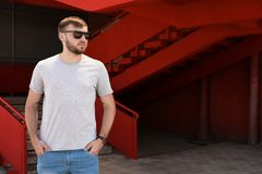 Young man wearing gray t-shirt on street. Urban style Royalty Free Stock Images