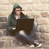 Young man in green hoodie using laptop on the steps Stock Images