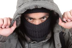 Young man wearing green jacket and a black hoodie. Mysterious man covering face with green jacket and black hoodie isolated on white Stock Photo