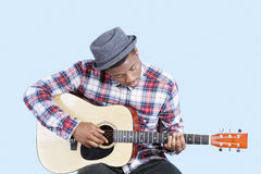 Young man wearing hat as he plays guitar over light blue background Royalty Free Stock Image