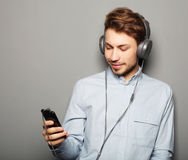 Young man wearing headphones and holding mobile phone Royalty Free Stock Photography