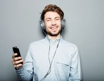 Young man wearing headphones and holding mobile phone Stock Photos