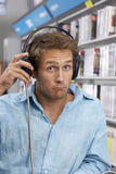 Young man wearing headphones, listening to CDs in record shop, looking disappointed, close-up, portrait Royalty Free Stock Image