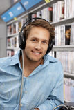 Young man wearing headphones, listening to CDs in record shop, smiling, close-up, portrait Royalty Free Stock Photo