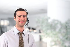 Young man wearing headset. Handsome smiling young man wearing an headset Royalty Free Stock Image