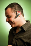 Young man wearing headset. A studio view of a young, smiling Hispanic man wearing a modern, wireless headset commonly used for hands free cellphone Stock Photography