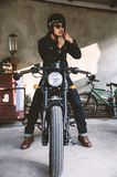 Man is wearing helmet on cafe racer motocycle. Young man is wearing helmet on cafe racer motocycle stock photo
