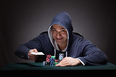 The young man wearing a hoodie with cards and chips gambling Stock Image