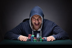 The young man wearing a hoodie with cards and chips gambling Royalty Free Stock Images
