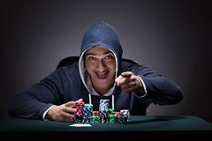 The young man wearing a hoodie with cards and chips gambling Stock Photo
