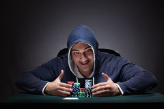The young man wearing a hoodie with cards and chips gambling Royalty Free Stock Photos