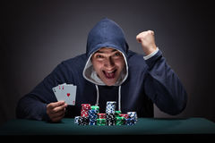 The young man wearing a hoodie with cards and chips gambling Royalty Free Stock Photography