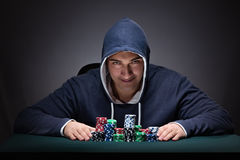 The young man wearing a hoodie with cards and chips gambling Stock Photos