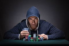 The young man wearing a hoodie with cards and chips gambling Stock Photography