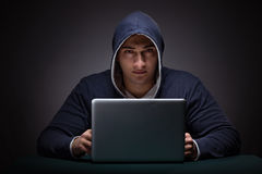 Young man wearing a hoodie sitting in front of a laptop computer Stock Photos