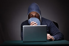 Young man wearing a hoodie sitting in front of a laptop computer. Gambling royalty free stock image
