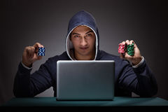 Young man wearing a hoodie sitting in front of a laptop computer. Gambling stock images