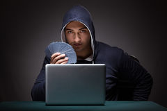 Young man wearing a hoodie sitting in front of a laptop computer. Gambling stock image