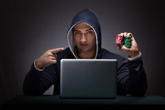 Young man wearing a hoodie sitting in front of a laptop computer Royalty Free Stock Photography
