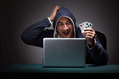 Young man wearing a hoodie sitting in front of a laptop computer Stock Image