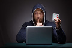 Young man wearing a hoodie sitting in front of a laptop computer Royalty Free Stock Image