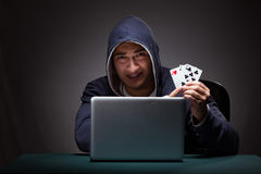 Young man wearing a hoodie sitting in front of a laptop computer Royalty Free Stock Images
