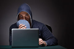 Young man wearing a hoodie sitting in front of a laptop computer. Gambling stock photo