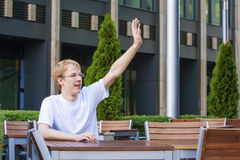 Young man wearing jacket sitting in restaurant and calling waite Royalty Free Stock Photo
