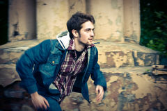 Young man wearing jeans clothes running. Young man running in front of the ruined wall. Captured motion with panning, motion blur Stock Photo