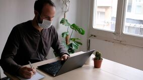 Young man wearing medical face mask in home office due to coronavirus spread, taking notes while working from computer in living