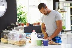 Young Man Wearing Pajamas Preparing Breakfast In Kitchen Stock Image