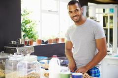Young Man Wearing Pajamas Preparing Breakfast In Kitchen Stock Photo