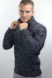 Young man wearing a pullover. Handsome blond man wearing a pullover over a grey background Royalty Free Stock Image
